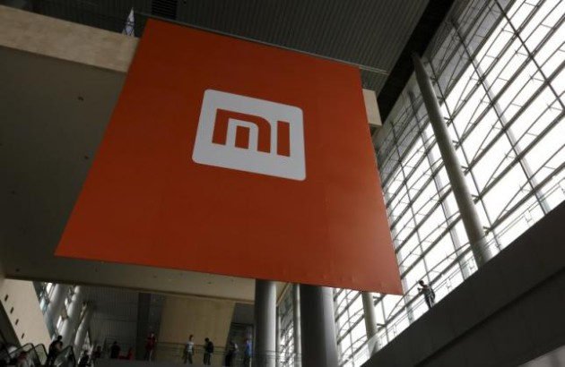 File picture of people standing near a logo of Xiaomi ahead of the launching ceremony of Xiaomi Phone 4, in Beijing